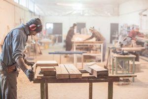 Man doing woodwork in carpentry / Carpenter work on wood plank i